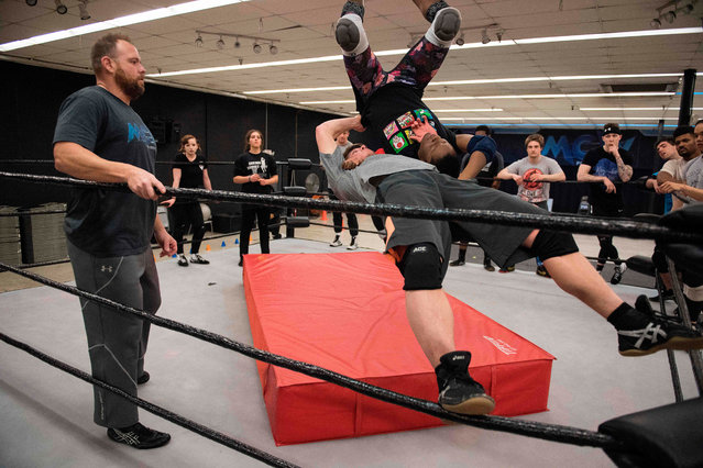 MCW Wrestling School Trainer RJ Meyer (L), a former champion pro wrestler, watches as professional wrestler Gia Scott is thrown from the top rope by one of her male counterparts during a class in Joppa, Maryland on April 5, 2018, at the MCW Wrestling school that teaches a budding wrestler the ins and outs of the industry. (Photo by Jim Watson/AFP Photo)