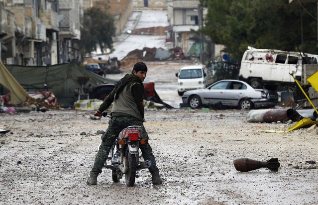 A man on a motorcycle rides past a mortar shell in the northern Syrian town of Kobani January 30, 2015. (Photo by Osman Orsal/Reuters)