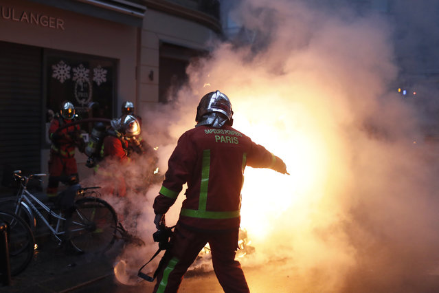 Firefighters try to extinguished a car set on fire by demonstrators during clashes with riot police, in Paris, France, Saturday, December 8, 2018. (Photo by Thibault Camus/AP Photo)