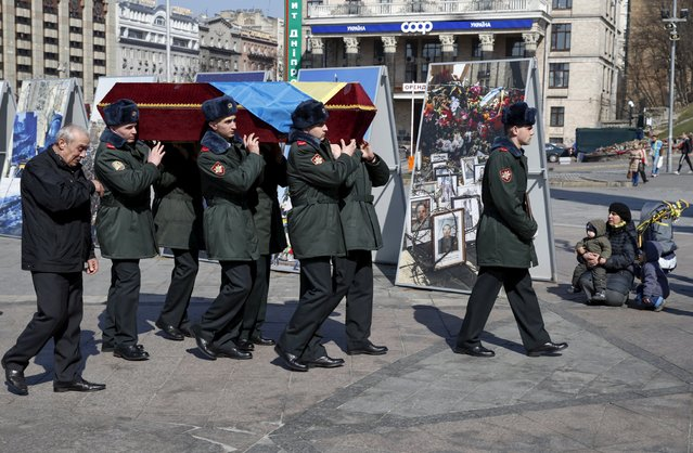 """Ukrainian honour guards carry the coffin bearing the body of Vadym Shalatovsky, a member of Defence Ministry's battalion """"Aydar"""", who was killed last year in the fighting near Luhansk in eastern Ukraine, during a funeral ceremony at Independence Square in central Kiev March 25, 2015. (Photo by Valentyn Ogirenko/Reuters)"""
