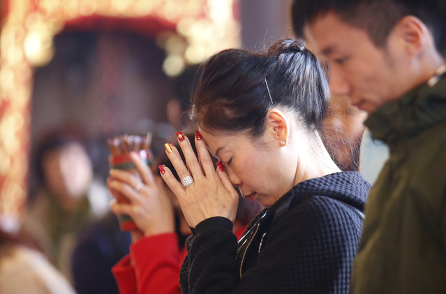 Chinese visitors pray during the celebration of the Lunar New Year at a temple in Hong Kong, Monday, February 8, 2016. (Photo by Kin Cheung/AP Photo)