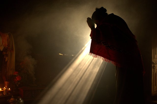 """""""Divine light"""". A women prostrates in a Buddhist monastery before to start a spiritual retreat. Once per year, the people from Helambu valley spend 3 days of meditation with one meal per day. Photo location: Helambu valley, Nepal. (Photo and caption by Marco Colombo/National Geographic Photo Contest)"""