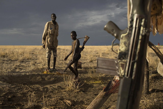A Turkana man and a boy carrying a gun look on as a G3 battle rifle hangs from a structure used to dry fish at a fishing camp on the shores of Lake Turkana, some kilometres from Todonyang near the Kenya-Ethiopia border in northwestern Kenya October 12, 2013. (Photo by Siegfried Modola/Reuters)