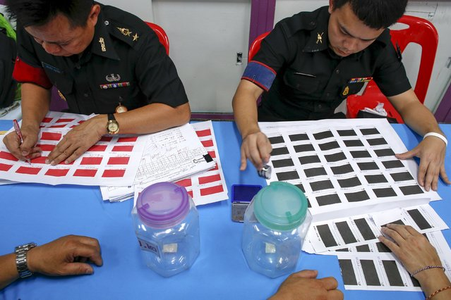 Military officers prepare black and red tickets during an army draft held at a school in Klong Toey, the dockside slum area in Bangkok April 5, 2015. (Photo by Athit Perawongmetha/Reuters)