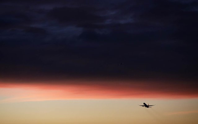 A plane takes off from the Los Angeles International Airport as clouds reflect the color of the sunset on Monday, December 2, 2013, in Los Angeles. (Photo by Jae C. Hong/AP Photo)