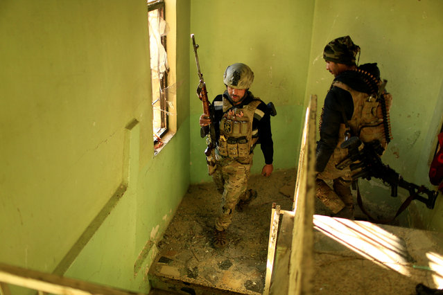Iraqi rapid response forces walk in the building during battle with Islamic State militants in the Mithaq district of eastern Mosul, Iraq, January 3, 2017. (Photo by Thaier Al-Sudani/Reuters)
