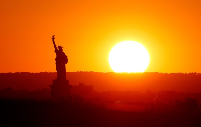 The sun sets behind the Statue of Liberty on August 2, 2021 in New York City. (Photo by Gary Hershorn/Getty Images)