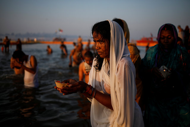 """Devotees pray after taking a holy dip at Sangam, the confluence of the Ganges, Yamuna and Saraswati rivers, during """"Kumbh Mela"""", or the Pitcher Festival, in Prayagraj, previously known as Allahabad, January 16, 2019. (Photo by Danish Siddiqui/Reuters)"""