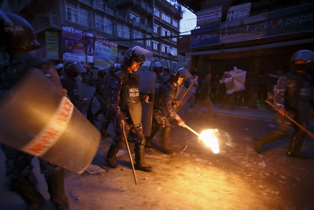 A Nepalese riot police personnel tries to douse a torch confiscated from the protester during the torch rally in Kathmandu April 6, 2015. (Photo by Navesh Chitrakar/Reuters)