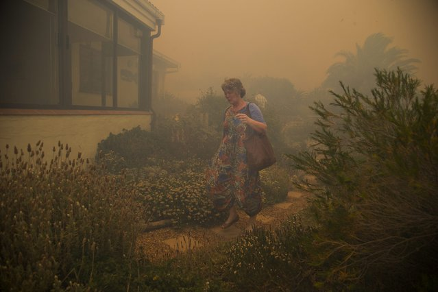 A resident evacuates from her home as a fire spreads rapidly through residential areas in the mountainous suburb of Simonstown in Cape Town, South Africa, 11 January 2017. Hundereds of residents are being evacuated as the fire fanned by strong north westerly winds started in Ocean View ripped through Glencairn heading towards Simonstown according to eye witness reports at the scene. (Photo by Nic Bothma/EPA)