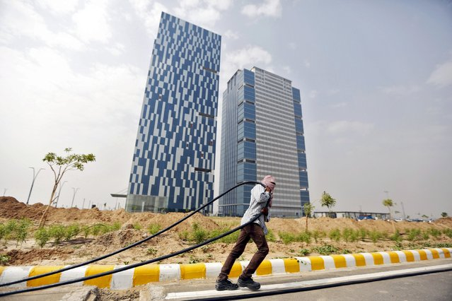 """A labourer pulls a cable in front of two office buildings in Gujarat International Finance Tec-City (GIFT) at Gandhinagar, in the western Indian state of Gujarat, April 10, 2015. India's push to accommodate a booming urban population and attract investment rests in large part with dozens of """"smart"""" cities like the one being built on the dusty banks of the Sabarmati river in western India. (Photo by Amit Dave/Reuters)"""