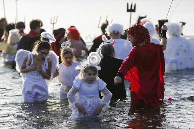"""People in costume celebrate in the frozen lake Orankesee during a so called """"Ice Carnival"""" event from winter swimming clubs in Berlin, January 14, 2017. (Photo by Markus Schreiber/AP Photo)"""