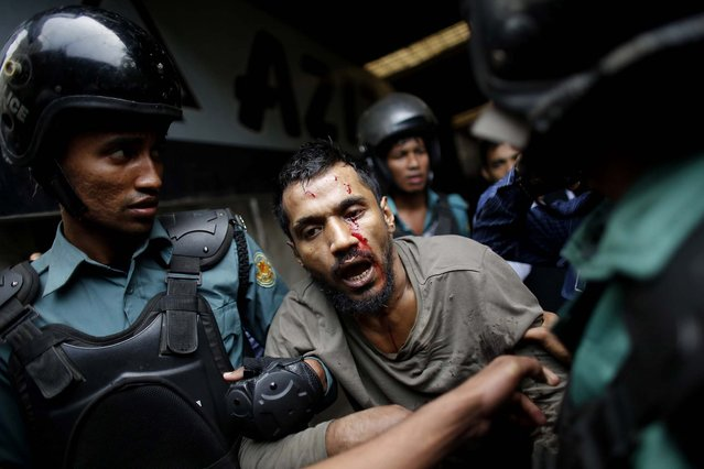 Police detain an injured man suspected of being an activist of the banned Islamist organization Hizb-ut-Tahrir, in Dhaka, Bangladesh, on December 27, 2013. Police arrested more than 18 activists suspected of being members of Hizb-ut-Tahrir, after a clash with police. (Photo by Andrew Biraj/Reuters)