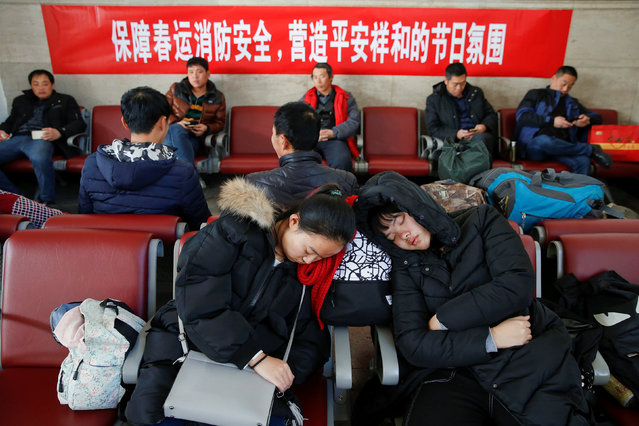 Passengers rest in front of a banner urging for fire protection during the Spring Festival at the departure hall of the Beijing Railway Station in central Beijing, China January 13, 2017 as the annual festival travel rush begins ahead of the Chinese Lunar New Year. (Photo by Damir Sagolj/Reuters)
