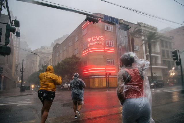 A group of people cross an intersection during Hurricane Ida on August 29, 2021 in New Orleans, Louisiana. Hurricane Ida made landfall earlier today and continues to cut across Louisiana. Hurricane Ida has been classified as a Category 4 storm with winds of 150 mph. (Photo by Brandon Bell/Getty Images)