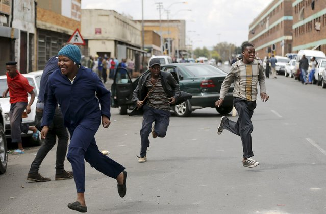 "Locals run after trying to rob a foreign motorist in Johannesburg, April 17, 2015. South Africa sought diplomatic support from countries across the continent on Friday to defeat the ""demon"" of anti-immigrant violence in which at least four people have been killed over the past fortnight. Foreign nationals have complained that the South African police are failing to protect them, raising the prospect of a row between Pretoria and its neighbours, as well as stirring hostility to South Africans working abroad. (Photo by Siphiwe Sibeko/Reuters)"