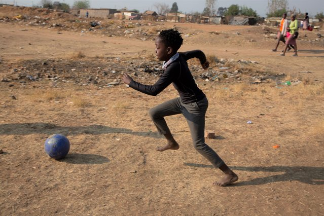A child plays soccer in the Diepsloot Township, north of Johannesburg, Thursday, August 26, 2021. (Photo by Denis Farrell/AP Photo)