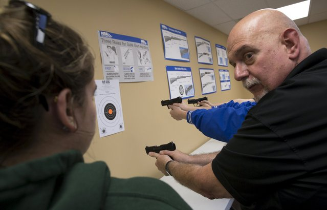 Instructor Wayne Inzerello (R) demonstrates how to hold a handgun to Savannah Garner during a Youth Handgun Safety Class at GAT Guns in East Dundee, Illinois, April 21, 2015. (Photo by Jim Young/Reuters)