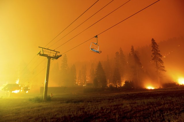 Seen in a long camera exposure, the Caldor Fire burns at the Sierra-at-Tahoe ski resort on Sunday, August 29, 2021, in Eldorado National Forest, Calif. The main buildings at the ski slope's base survived as the main fire front passed. (Photo by Noah Berger/AP Photo)