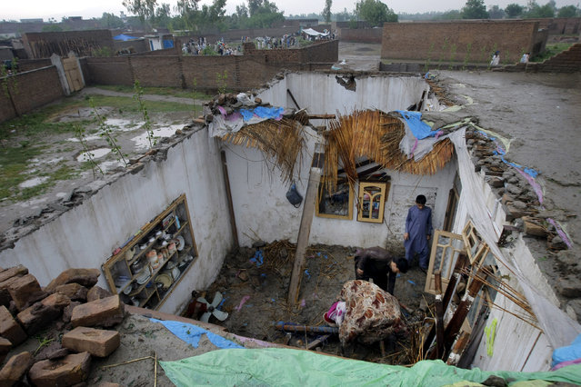 People collect their belonging from a house damaged from heavy rain and windstorm that reached up to a speed of 120 kph (75 mph) Sunday evening which collapsed hundreds of buildings, uprooted trees, and electric poles, in Peshawar, Pakistan, Monday, April 27, 2015. (Photo by Mohammad Sajjad/AP Photo)