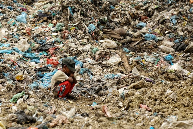 The son of a garbage collector rests as his father (not pictured) looks for items that can be resold, at a landfill site in Alue Liem in Lhokseumawe on September 15, 2021. (Photo by Azwar Ipank/AFP Photo)