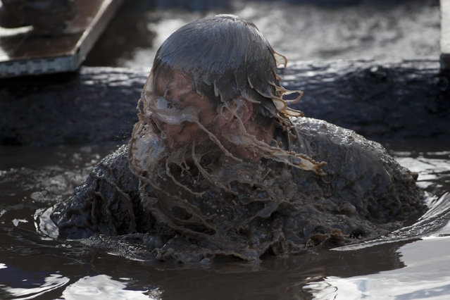 """A competitor makes his way through an obstacle during the annual Tough Guy race """"the toughest race in the world"""" at Perton in Staffordshire, England, Sunday Jan. 26, 2014. (Photo by Jon Super/AP Photo)"""