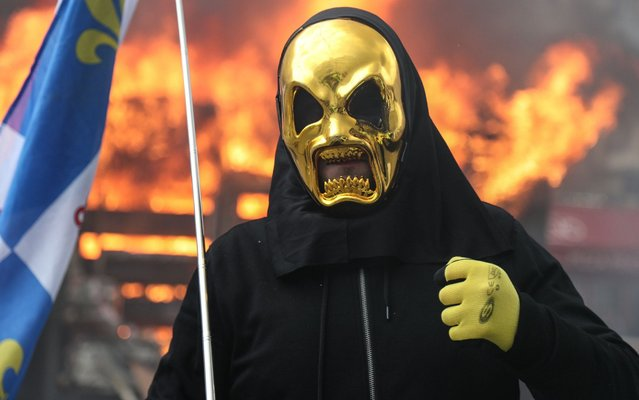 """A Yellow Vest protester wearing a gold mask takes part in Paris on March 16, 2019, in the 18th consecutive Saturday of demonstrations called by the """"Yellow Vest"""" (gilets jaunes) movement. Demonstrators hit French city streets again on March 16, for a 18th consecutive week of nationwide protest against the French President's policies and his top-down style of governing, high cost of living, government tax reforms and for more """"social and economic justice"""". (Photo by Zakaria Abdelkafi/AFP Photo)"""