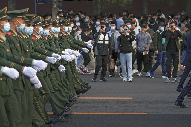 People film paramilitary policemen march on a street to disperse the crowds near Tiananmen Square after a flag raising ceremony on National Day in Beijing, Friday, October 1, 2021. Hundreds of thousands of people watched a flag-raising ceremony near Tiananmen Square Friday morning to celebrate the 72nd National Day of the People's Republic of China. (Photo by Andy Wong/AP Photo)