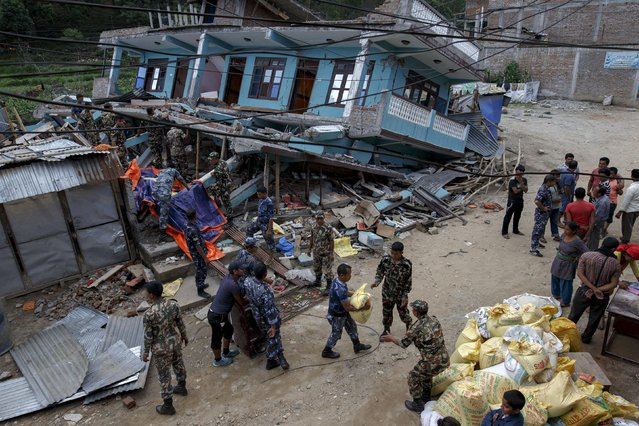 Nepalese military personnel try to salvage supplies among the debris of a damaged shop at a devastated area following Saturday's earthquake at Arugat village, near Gorkha, Nepal April 29, 2015. (Photo by Athit Perawongmetha/Reuters)