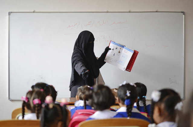 A teacher gives lesson to schoolgirls in a classroom at a school that reopened after a gap of more than a year because of clashes in Benghazi, Libya April 20, 2015. After a year of war, Libya's second-largest city Benghazi is divided into areas controlled by forces loyal to one of two rival Libyan governments, and areas held by Islamist fighters led by the group Washington blames for the 2012 attack that killed its ambassador. (Photo by Esam Omran Al-Fetori/Reuters)