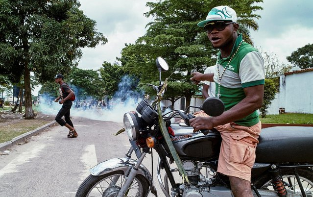 A moto-taxi driver reacts as riot police fire teargas towards anti-government protesters gathered to mourn in the neighborhood of veteran Congolese opposition leader Etienne Tshisekedi of the Union for Democracy and Social Progress (UDPS) in the Limete Municipality of the Democratic Republic of Congo's capital Kinshasa, February 2, 2017. (Photo by Robert Carrubba/Reuters)