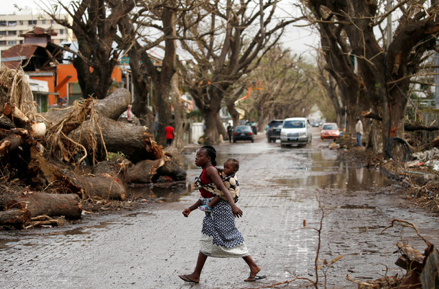 A woman crosses the road with a baby on her back after Cyclone Idai in Beira, Mozambique, March 23, 2019. The death toll in Mozambique on March 23, 2019 climbed to 417 after a cyclone pummelled swathes of the southern African country, flooding thousands of square kilometres, as the UN stepped up calls for more help for survivors. Cyclone Idai smashed into the coast of central Mozambique last week, unleashing hurricane-force winds and rains that flooded the hinterland and drenched eastern Zimbabwe leaving a trail of destruction. (Photo by Siphiwe Sibeko/Reuters)