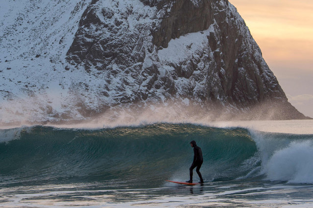 A surfer rides a wave at the snowy beach of Unstad, in Lofoten Island, Arctic Circle, on March 9, 2016. (Photo by Olivier Morin/AFP Photo)