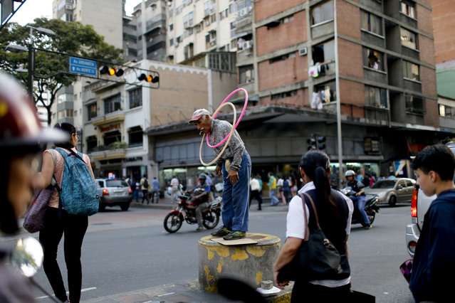 In this Monday, March 18, 2019 photo, a street artist performs in Caracas, Venezuela. Venezuelans are facing a severe economic and political crisis as President Nicolas Maduro has remained in power despite heavy pressure from the United States and other countries arrayed against him, managing to retain the loyalty of most of Venezuela's military leaders. (Photo by Natacha Pisarenko/AP Photo)