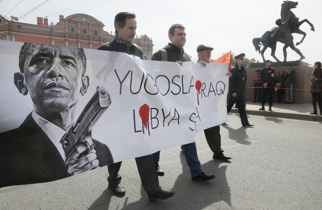 Communists carry a poster depicting U.S. President Barack Obama during a traditional May Day march in St.Petersburg, Russia, Friday, May 1, 2015. (Photo by Dmitry Lovetsky/AP Photo)