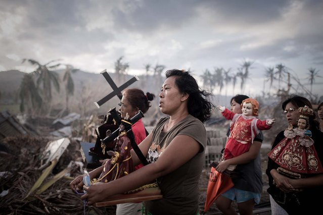1st prize in the Spot News Single category. Phillipe Lopez, France, for Agence France-Presse. The photo shows survivors of typhoon Haiyan marching during a religious procession in Tolosa, on the eastern island of Leyte, Philippines, November 18, 2013. One of the strongest cyclones ever recorded, Haiyan left 8,000 people dead and missing and more than four million homeless after it hit the central Philippines. (Photo by Phillipe Lopez/World Press Photo)