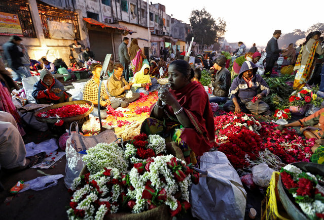 A vendor drinks water as she waits for customers at a roadside flower market in Ahmedabad, India, February 8, 2017. (Photo by Amit Dave/Reuters)