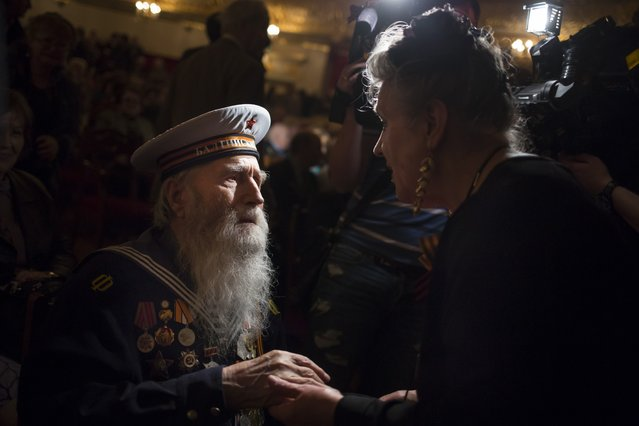 Georgy Shirokov, 91, Russian veteran of WWII and former sailor of the Baltic Fleet, left, is helped by a Bolshoi Theater employee to take his seat prior to a concert celebrating the 70th anniversary of victory in WWII, in Moscow, Russia, Friday, May 1, 2015. (Photo by Alexander Zemlianichenko/AP Photo)
