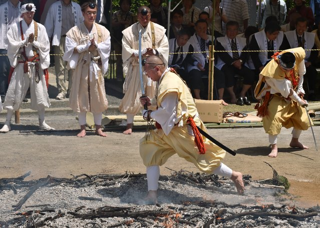 "A Buddhist monk takes part in the traditional ""hi-watari"", or fire-walking ritual, at Shiofune-kannonji temple in Ome City, Tokyo on May 3, 2015. Hundreds of people followed Buddhist ascetics and participated in fire walking to ""purify the mind and body"" and to pray for good health and safety. (Photo by Kazuhiro Nogi/AFP Photo)"
