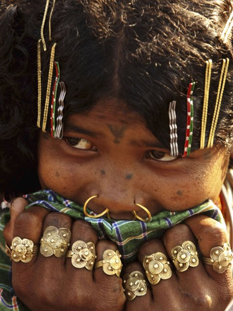 A member of Indiaís Dongria tribe wearing traditional ornaments watches others dance during the two-day long Niyamraja Festival atop of the Niyamgiri hills near Lanjigarh in Kalahandi district, Orissa state. (Photo by Biswaranjan Rout/AP Photo)
