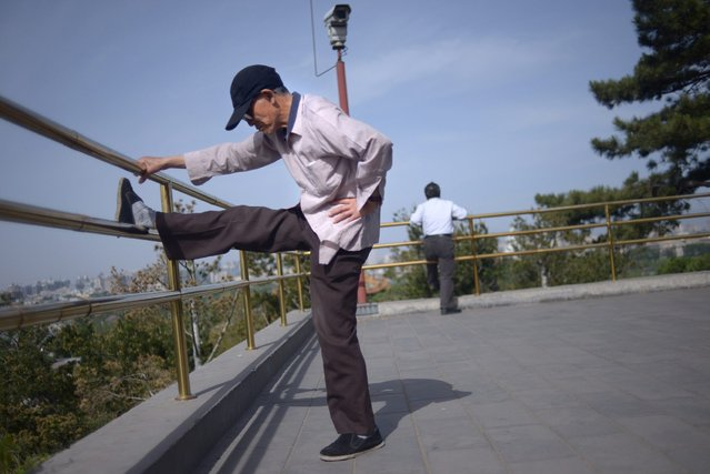 An elderly man does physical exercise at a park near the Forbidden City in Beijing on May 3, 2015. (Photo by Wang Zhao/AFP Photo)