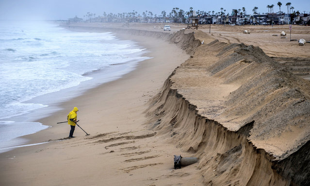 Stan Ross of Newport Beach digs up some sand near the Balboa Pier in Newport Beach, Calif., early Saturday, February 18, 2017, as he looks for coins and jewelry following Friday's storm that eroded the beach, brought high winds, and heavy rain which flooded many areas in Southern California. (Photo by Mark Rightmire/The Orange County Register via AP Photo)