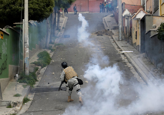 A riot policeman launches a tear gas canister towards coca growers from Yungas during the clashes in La Paz, Bolivia, February 21, 2017. (Photo by David Mercado/Reuters)