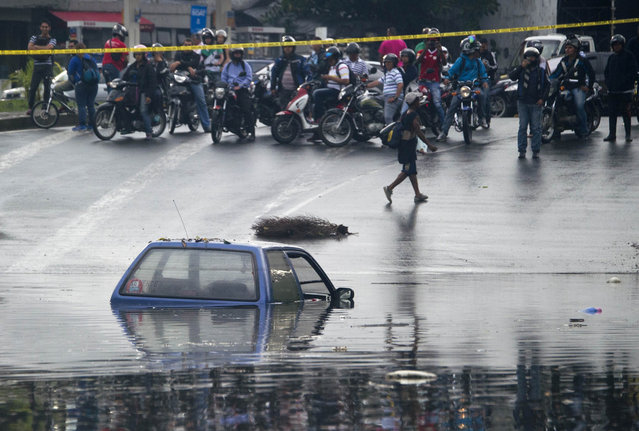 People look at a car on a flooded street in Cali, Colombia on March 12, 2014, during heavy rains. The IDEAM (Institute of Hydrology, Meteorology and Environmental Studies of Colombia) announces a strong rainy season for the next three months in the country. (Photo by Luis Robayo/AFP Photo)