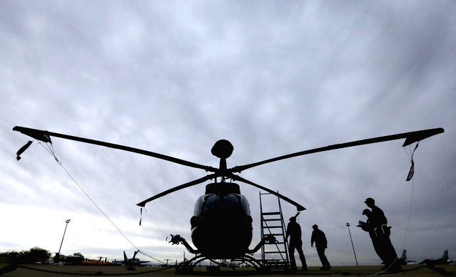 Crew from the 309th Aerospace Maintenance and Regeneration Group boneyard prepare to remove engine fluid from a Bell OH-58 Kiowa helicopter after its arrival at Davis-Monthan Air Force Base in Tucson, Ariz. on Friday, May 15, 2015. The OH-58 has been in continuous use by the U.S. Army since 1969 and seen combat in every conflict since Vietnam. (Photo by Matt York/AP Photo)