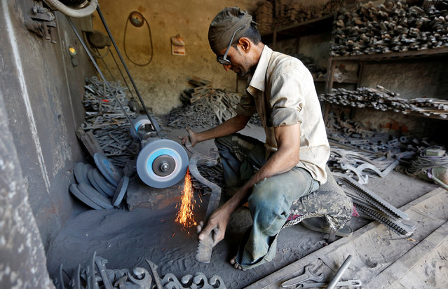 A worker grinds a gear rod used in a textile machine inside a small scale manufacturing unit in Ahmedabad, India, April 12, 2016. India's industrial output grew at an annual rate of 2.0 percent in February, government data showed on Tuesday. (Photo by Amit Dave/Reuters)