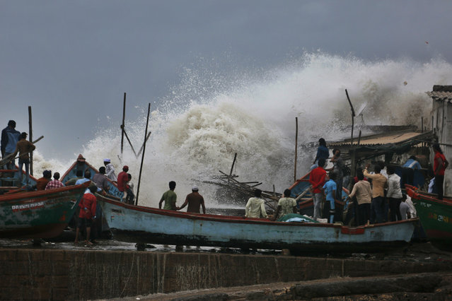 A waves crashes as people stand on boats on the Arabian Sea coast in Veraval, Gujarat, India, Wednesday, June 12, 2019. Indian authorities evacuated tens of thousands of people on Wednesday as a severe cyclone in the Arabian Sea approached the western state of Gujarat, lashing the coast with high winds and heavy rainfall. (Photo by Ajit Solanki/AP Photo)