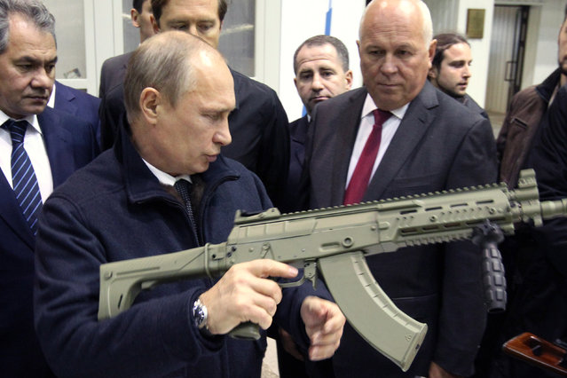 Russian President Vladimir Putin (L) holds a Kalashnikov machine gun during his visit to the Kalashnikov manufacturing plant September 18, 2013 in Izhevsk, Russia. (Photo by Sasha Mordovets/Getty Images)
