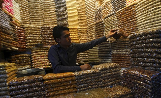 A shopkeeper arranges dry fruit bags at his shop in Peshawar, Pakistan May 18, 2015. (Photo by Fayaz Aziz/Reuters)