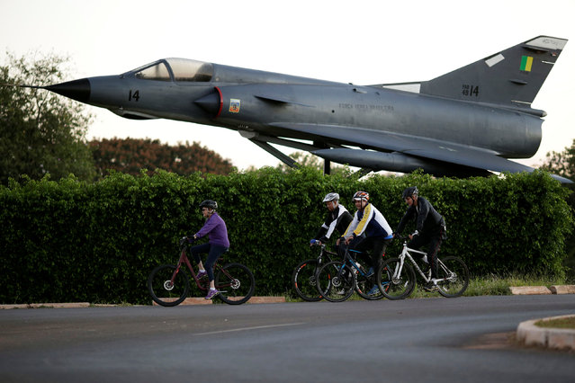 Brazil's President Dilma Rousseff rides her bicycle accompanied by bodyguards near the Alvorada Palace in Brasilia, Brazil April 15, 2016. (Photo by Ueslei Marcelino/Reuters)